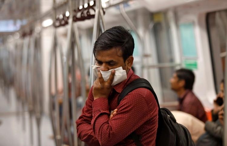 Un pasajero se protege con un pañuelo en el metro de Nueva Delhi. (REUTERS/Anushree Fadnavis)