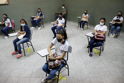 Estudiantes del Colegio Presidente Franco permanecen en sus asientos con la debida distancia como parte del protocolo sanitario contra la covid-19 durante el inicio de las clases presenciales en Asunción (Paraguay). EFE/Nathalia Aguilar/Archivo