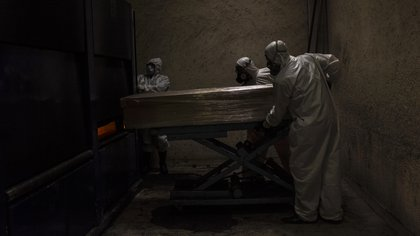 24/06/2020 FILED - 24 June 2020, Mexico, Mexico City: Employees in protective suits carry a coffin of a person who died with a coronavirus infection before his funeral. Photo: Jacky Muniello/dpa