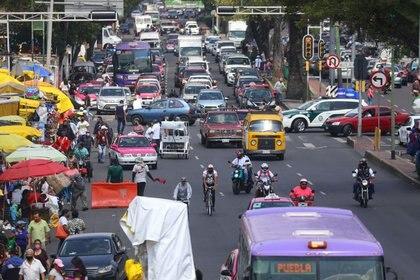 Las personas y los automóviles aparecen en una avenida durante el inicio de la reapertura gradual de las actividades comerciales, mientras continúa el brote en Ciudad de México (Reuters)
