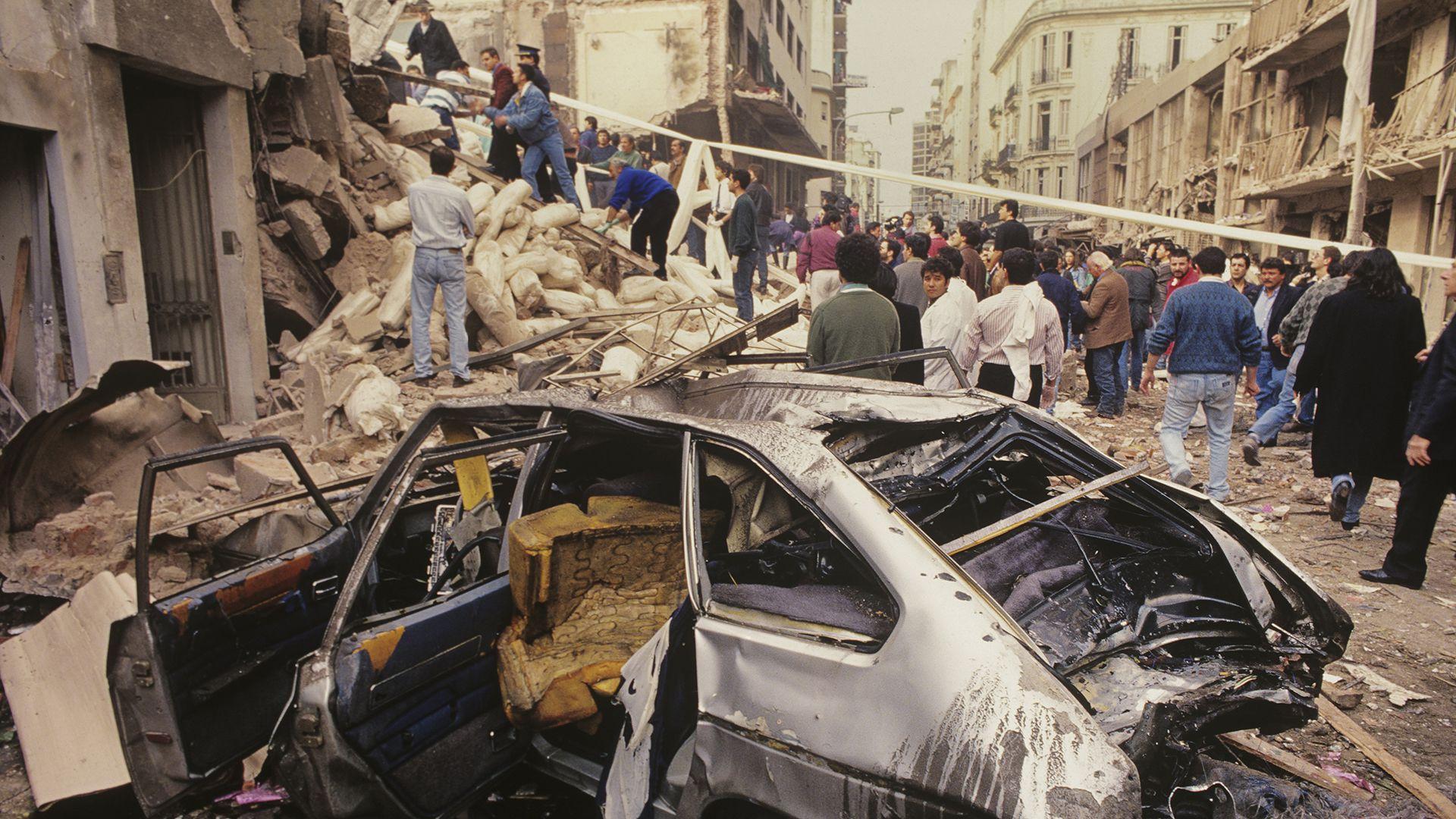 """""""Esta imagen da un poco de magnitud del atentado. Fue una fotografía muy usada por los medios porque el primer plano del coche destruido genera muchas lecturas"""" (Julio Menajovsky)"""