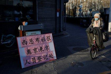Una mujer va al trabajo en bicicleta Beijing, China January 31, 2020. REUTERS/Carlos Garcia Rawlins