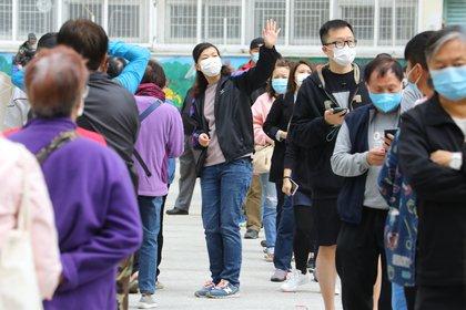 Un grupo de residentes de uno de los edificios en los que se ha localizado un último brote de la COVID-19 en Hong Kong hace turno para someterse a una prueba de coronavirus