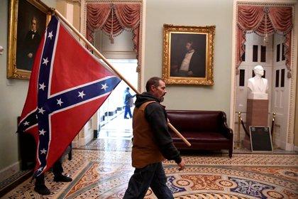 Un activista con la bandera confederada camina por los pasillos internos del Capitolio. El plan era impedir a cualquier precio que Joe Biden sea certificado como nuevo presidente norteamericano. No lo lograron y el Capitolio impuso su legalidad (Reuters)