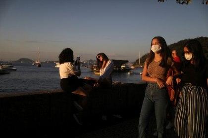 Jóvenes disfrutan del atardecer frente a un bar en el barrio carioca de Urca en medio del brote de COVID-19 en Río de Janeiro, Brasil, 8 de agosto de 2020 (REUTERS/Pilar Olivares)