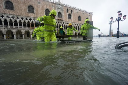 Venice (Italy), 12/11/2019.- Workers wade through floodwaters in Venice, Italy, 12 November 2019. The high tide has already reached the level of 1 meter above sea level in Venice at 8 am. (Italia, Niza, Venecia) EFE/EPA/ANDREA MEROLA