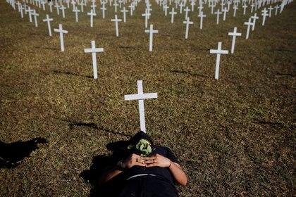 Un activista yace junto a las cruces que simbolizan a los que murieron a causa de la enfermedad del coronavirus (COVID-19) frente al Congreso Nacional durante una protesta contra Bolsonaro, este domingo en Brasilia (REUTERS / Adriano Machado)