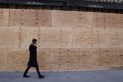 Un hombre pasa por delante de un comercio tapiado en Nueva York. Foto: REUTERS/Carlo Allegri