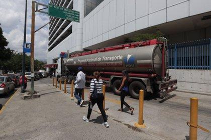 Un camión cisterna distribuye combustible en una estación de servicio de Caracas (EFE/Rayner Peña)