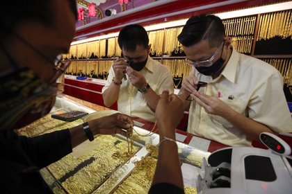 Tasadores de oro en una tienda de Bangkok. EFE/EPA/RUNGROJ YONGRIT