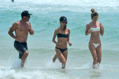 All terrain. Alessandra Ambrosio took a gym class in the sea. She was seen training on the beaches of Florianópolis, in her native Brazil. The model and a friend followed the instructions of their personal trainer in a very demanding routine