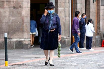 Una vendedora ecuatoriana con tapabocas es vista mientras camina este miércoles en una calle de Quito (Ecuador). EFE/José Jácome/Archivo