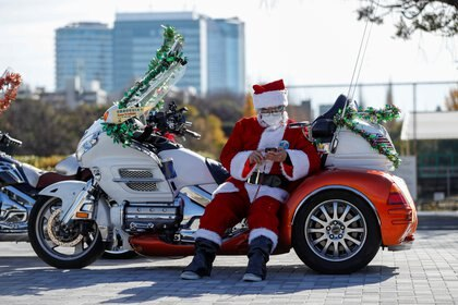 Un hombre disfrazado de Papá Noel con una máscara protectora se detiene antes del desfile de la Carrera de Juguetes de Navidad organizado por el Club Harley de Papá Noel en Tokio, Japón (REUTERS/Issei Kato)