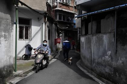 Un hombre monta una bicicleta eléctrica en una zona residencial de Wuhan, el epicentro del nuevo brote de coronavirus, provincia de Hubei, el 4 de marzo de 2020 (REUTERS/Stringer)