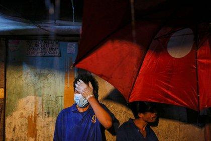Funerarios se preparan para entrar en una casa de Manila, donde la policía y los testigos dijeron que cinco sospechosos de drogas fueron muertos a tiros por pistoleros no identificados (Reuters)