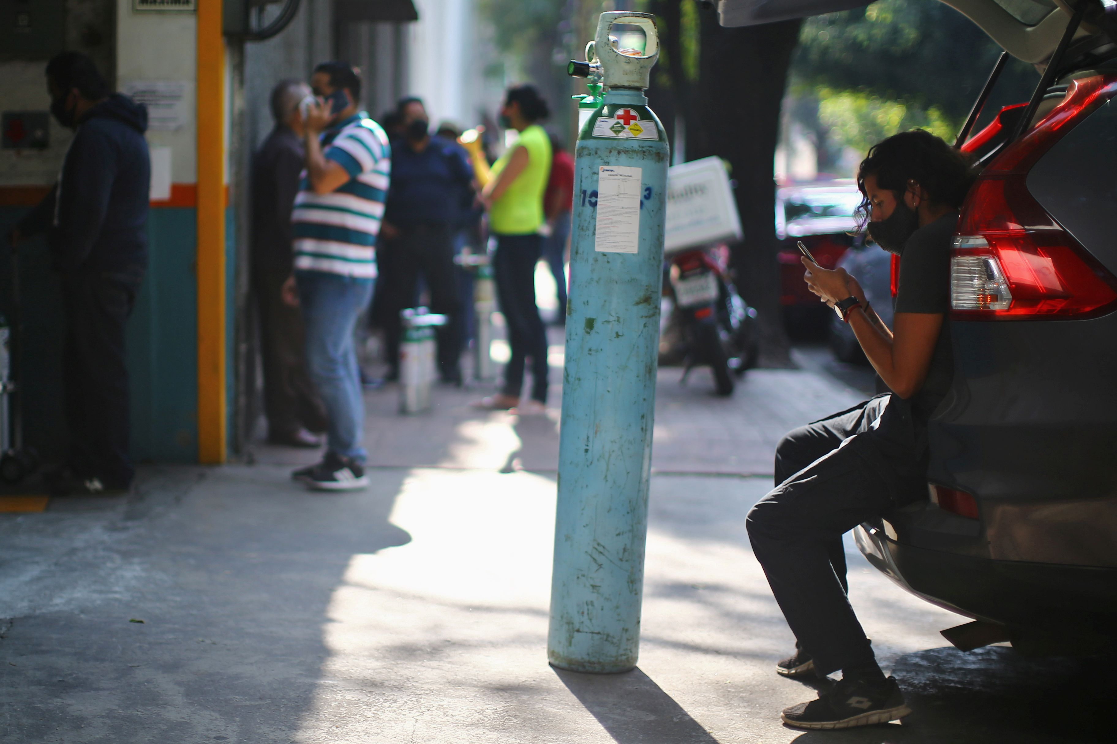 A man queues to fill an oxygen tank outside a medical supply store in Mexico City, December 21, 2020.
