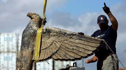 En esta fotografía de archivo del 10 de febrero de 2006, un trabajador uruguayo dirige el rescate del águila del acorazado alemán de la Segunda Guerra Mundial, Graf Spee, en Montevideo, Uruguay. (AP Foto / Marcelo Hernández, Archivo)