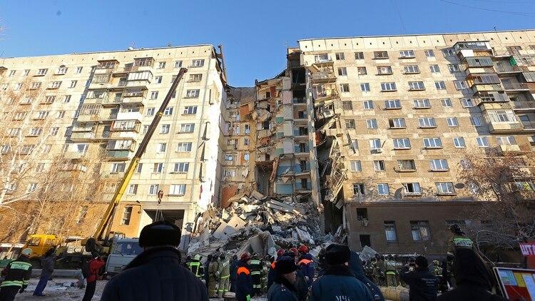 El espacio vacío donde estaba el edificio y los escombros debajo (AP)