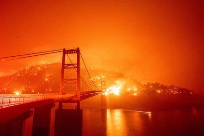 El puente Bidwell Bar está rodeado por el fuego en el lago Oroville durante el incendio Bear en Oroville, California. (Photo by JOSH EDELSON / AFP)