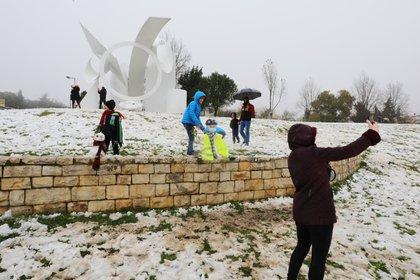 La gente juega con la nieve y se toman selfies durante una mañana nevada en Jerusalén, el 18 de febrero de 2021. REUTERS / Ammar Awad