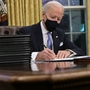 Joe Biden prepares to sign a series of executive orders in the Oval Office on Jan. 20.