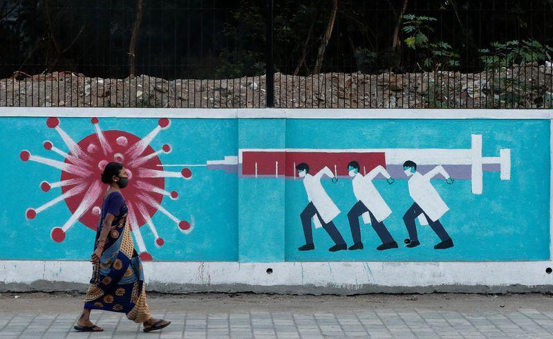 Una mujer con mascarilla camina frente a un mural que representa un coronavirus y varios médicos combatiéndolo con una jeringa gigante en Bombay, la India, el 30 de marzo de 2021. (REUTERS/Francis Mascarenhas)