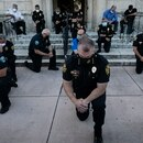 Police officers kneel during a rally in Coral Gables, Florida on May 30, 2020 in response to the recent death of George Floyd, an unarmed black man who died while being arrested and pinned to the ground by a Minneapolis police officer. - Clashes broke out and major cities imposed curfews as America began another night of unrest Saturday with angry demonstrators ignoring warnings from President Donald Trump that his government would stop violent protests over police brutality