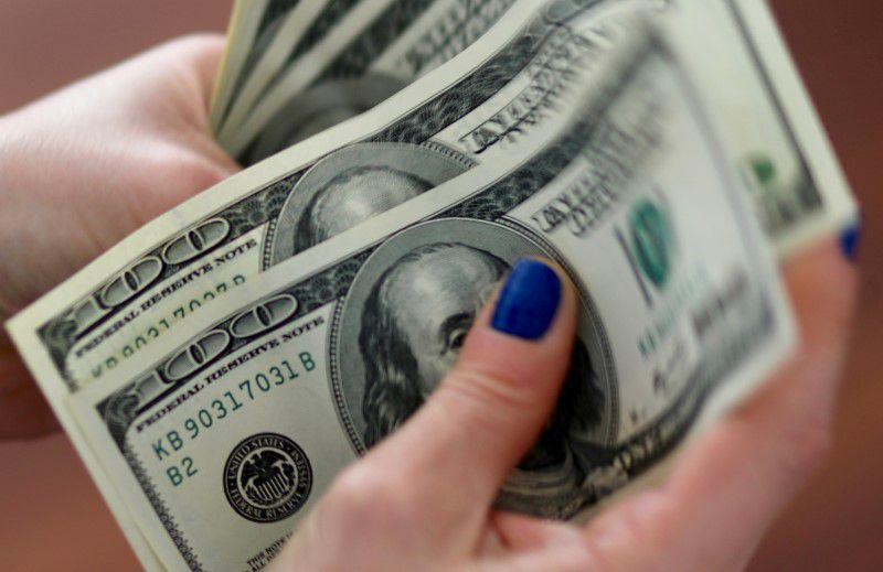 Foto de archivo - Una mujer cuenta billetes de cien dólares estadounidenses, en Buenos Aires, Argentina. Aug 28, 2018. REUTERS/Marcos Brindicci