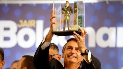 Jair Bolsonaro levanta un muñeco de él con la banda presidencial y sosteniendo un fusil de asalto, durante un acto en Curitiba (Reuters/ Rodolfo Buhrer)