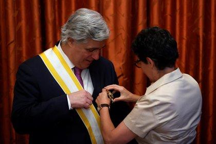 La ministra de Asuntos Exteriores, Arancha González Laya, coloca a su homólogo de Uruguay, Francisco Bustillo, la Gran Cruz de Isabel la Católica, hoy en la sede del Ministerio, en Madrid. EFE/Mariscal