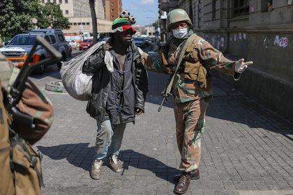 Un miembro de las Fuerzas de Defensa Nacional de Sudáfrica hace un gesto a un hombre sin hogar durante el primer día de un encierro nacional de 21 días para tratar de contener el brote de coronavirus (COVID-19) en Johannesburgo, Sudáfrica, el 27 de marzo de 2020. (REUTERS/Siphiwe Sibeko)