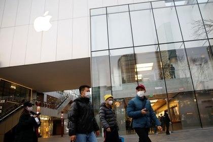 Personas con máscaras faciales, pasan por delante de una tienda de Apple en un centro comercial, mientras el país es golpeado por un brote del nuevo coronavirus, en Pekín, China, el 18 de febrero de 2020 (REUTERS/Carlos García Rawlins)
