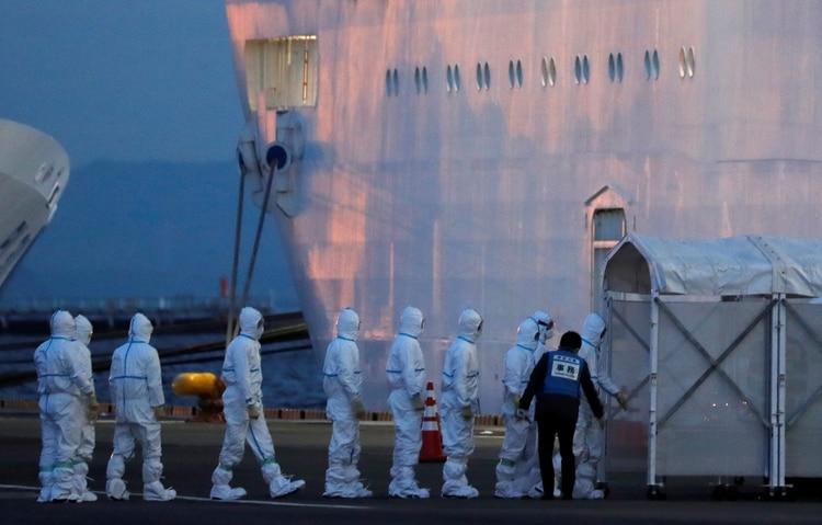 Oficiales con trajes de protección entran a la nave para revisar a los pacientes (Reuters)