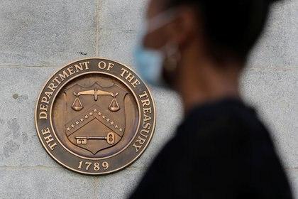 Imagen de archivo de una persona con mascarilla pasando frente al sello del Departamento del Tesoro en la sede central de Washington, D.C., EEUU. 29 agosto 2020. REUTERS/Andrew Kelly