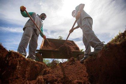 Trabajadores colocan arena en una tumba hoy, en el cementerio Campo de Esperanza, en Brasilia (EFE/Joédson Alves)