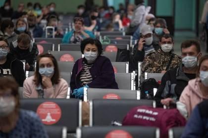 Viajeros con mascarilla esperan en el vestíbulo de la estación de tren en Kazansky, en Moscú. EFE/EPA/SERGI ILNITSKY
