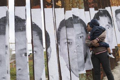 La frontera separa a esta madre y su hijo del territorio al que aspiran ingresar (AP /Hans-Maximo Musielik)