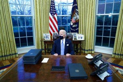 Biden junto a sus primeros decretos. Foto: REUTERS/Tom Brenner