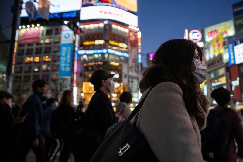 Una mujer con una marcarilla protectora en el cruce de caminos en el distrito comercial de Shibuya en Tokio (REUTERS/Athit Perawongmetha)