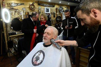 El líder del opositor Partido Laborista británico Jeremy Corbyn se corta la barba en el marco de un acto de campaña en Carmarthen, el 7 de diciembre de 2019 (REUTERS/Rebecca Naden)
