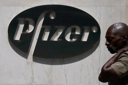 Un hombre pasa por el frente de la farmacéutica Pfizer, que produce una de las vacunas candidatas contra COVID-19 (REUTERS/Carlo Allegri/File Photo)