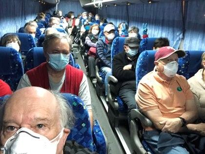 Pasajeros evacuados del crucero, a bordo de un bus que los trasladó desde Yokohama al aeropuerto de Haneda (Reuters)