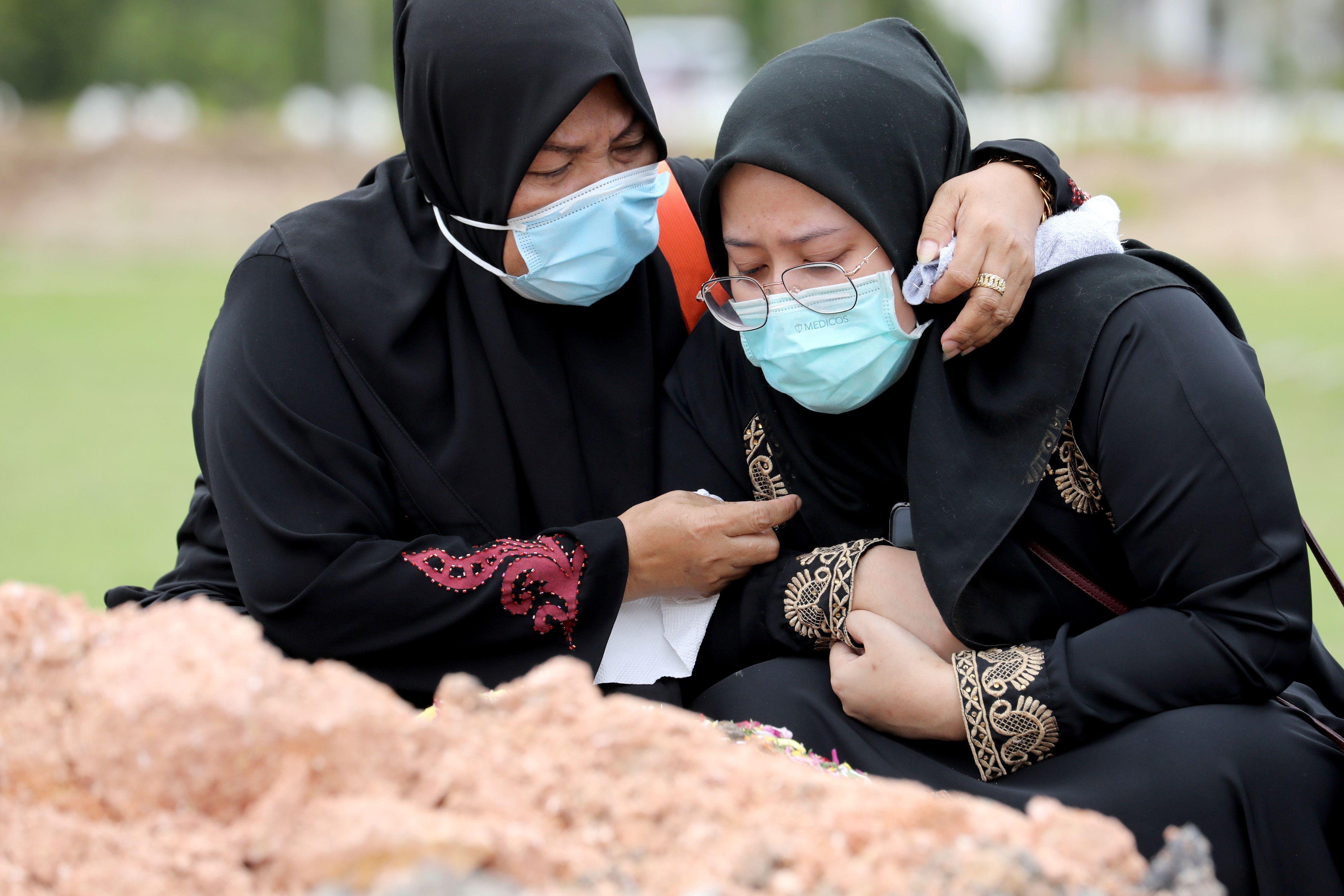 Dos mujeres lloran la muerte de un familiar en un cementerio de Batu Caves, Malasia. (REUTERS/Lim Huey Teng)