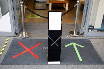 Un cartel con reglas de distanciamiento y entrada en Berlín, Alemania (REUTERS/Axel Schmidt/Foto de archivo)