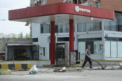 Imagen de archivo de un hombre pasando por una gasolinera cerrada de PDVSA en San Cristóbal (Reuters)