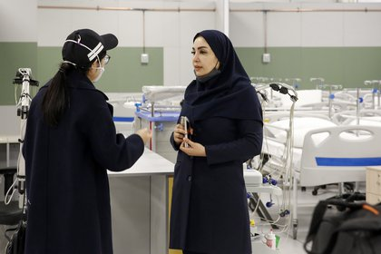 An Iranian health inspector checks a makeshift hospital set up inside the Iran Mall, northwest of Tehran, on March 21, 2020 amid the coronavirus outbreak. - Iran said that 123 more people had died from coronavirus, raising the official death toll to 1,556 in the Islamic republic, one of the world's worst affected countries. (Photo by STR / AFP)