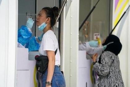 Trabajadores sanitarios toman muestras de hisopos nasales de residentes locales para una prueba de COVID-19 en Tailandia
