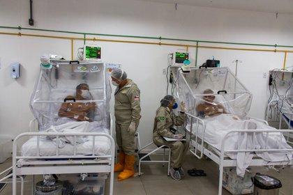 Enfermeras controlan a los pacientes en la unidad de cuidados intensivos del hospital de campaña municipal de Gilberto Novaes. El hospital se creó en una escuela y tiene 180 camas, incluidas 38 camas de cuidados intensivos. 4 de junio.