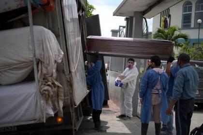 Trabajadores suben ataúdes para ser trasladados a Guayaquil