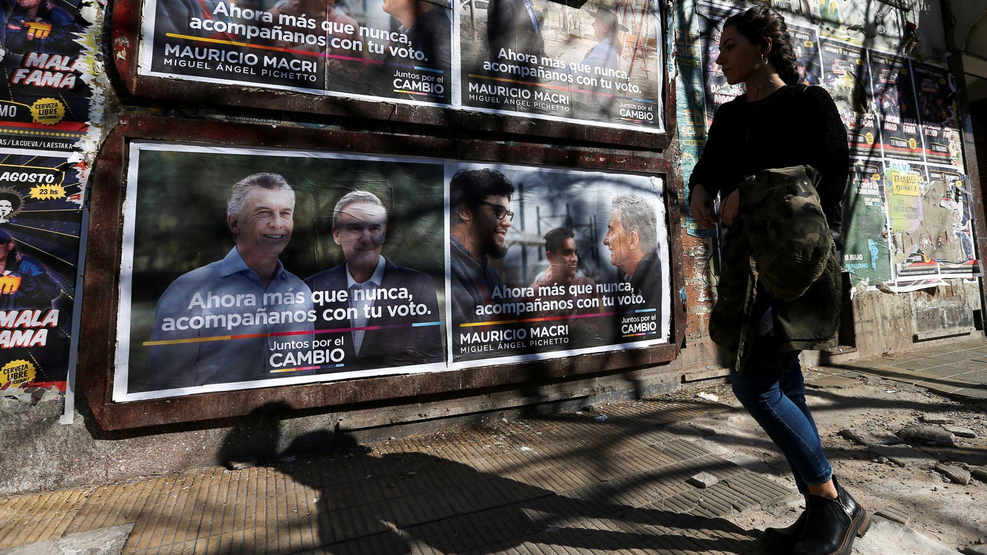 Una mujer camina por una calle frente a una publicidad de Mauricio Macri. (Reuters)